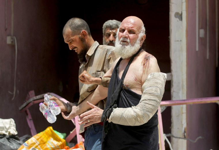 Image: An injured Iraqi wearing a cast and sling over his left arm evacuates from the Old City of Mosul on June 30.