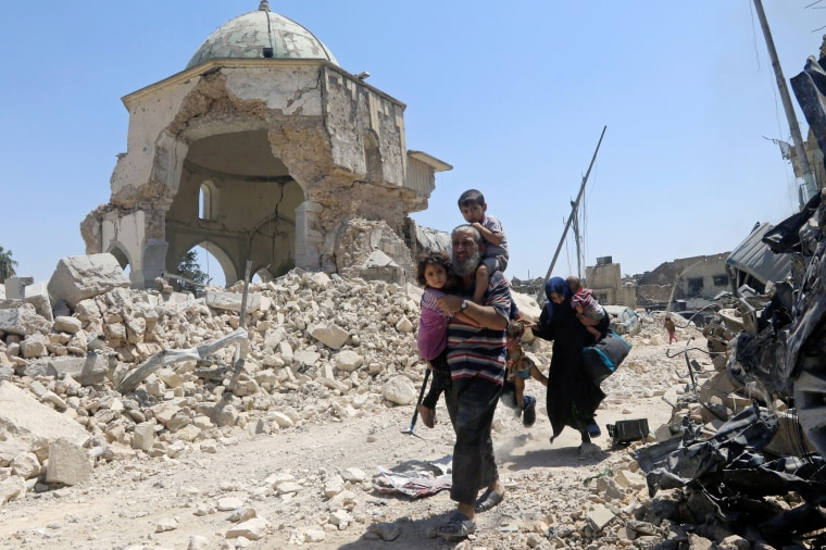 Image: Displaced Iraqi civilians walk past the ruined Grand al-Nuri Mosque after fleeing their homes on June 30.