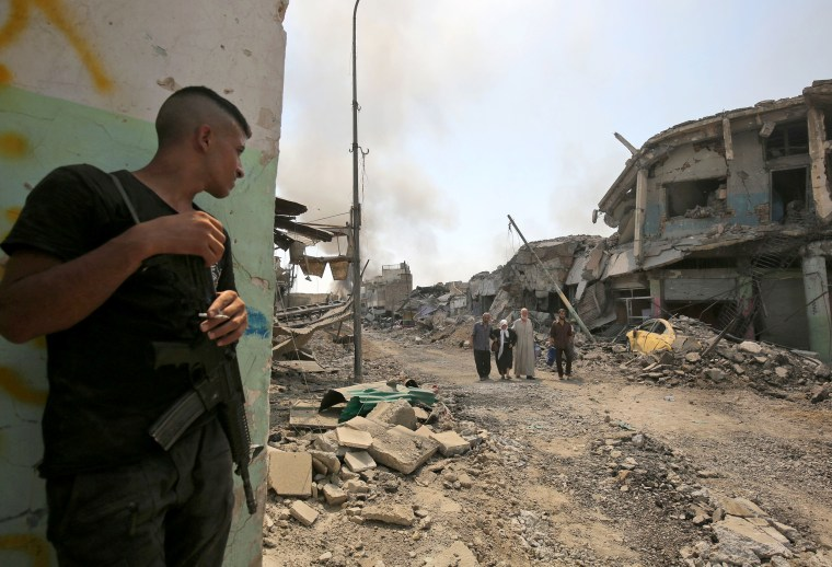 Image: A member of the Iraqi forces smokes a cigarette as he watches Iraqis evacuating from the Old City of Mosul on June 30, during the offensive to retake the city from Islamic State fighters.