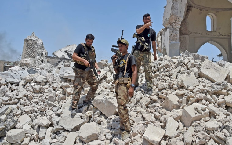Image: Members of the Iraqi Counter-Terrorism Service stand over the rubble of the destroyed Al-Nuri Mosque on June 30.