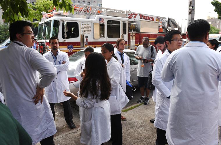 Image: Hospital staff stand outside the Bronx-Lebanon Hospital