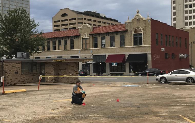Image: An investigator collects evidence near an Arkansas nightclub