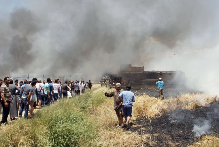 Image: Smoke billows as Syrians refugees attempt to extinguish a massive fire in a camp for refugees near the village of Qab Elias in the Lebanese Bekaa valley on July 2, 2017.