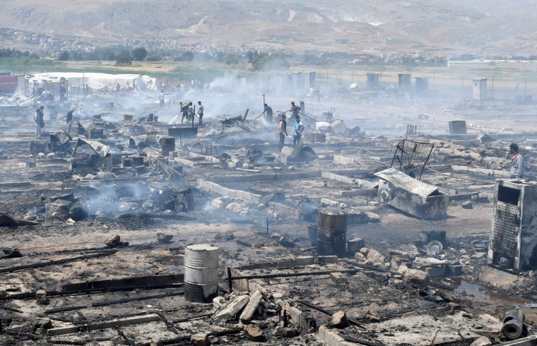 Image: Civil defense members and civilians put out fire at a camp for Syrian refugees near the town of Qab Elias, in Lebanon's Bekaa Valley, July 2, 2017.