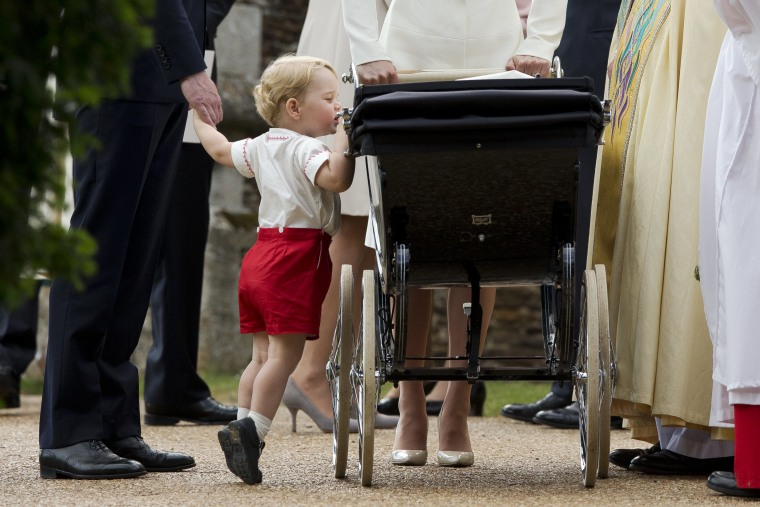 Britain's Prince George gets up on tiptoes to peek into the pram of Princess Charlotte flanked by his parents Prince William and Kate the Duchess of Cambridge as they leave after Charlotte's Christening at St. Mary Magdalene Church in Sandringham, England, Sunday, July 5, 2015.