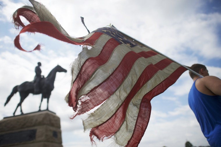 Image: William Gillis carries a tattered flag besides a battlefield monument as activists gather at the Gettysburg National Military Park
