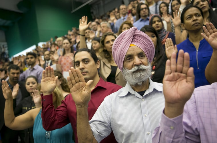 Image: Guillermo Leal, left, of Mexico, and Mohinder Singh, of India, take the oath of citizenship at a naturalization ceremony in Austin, Texas