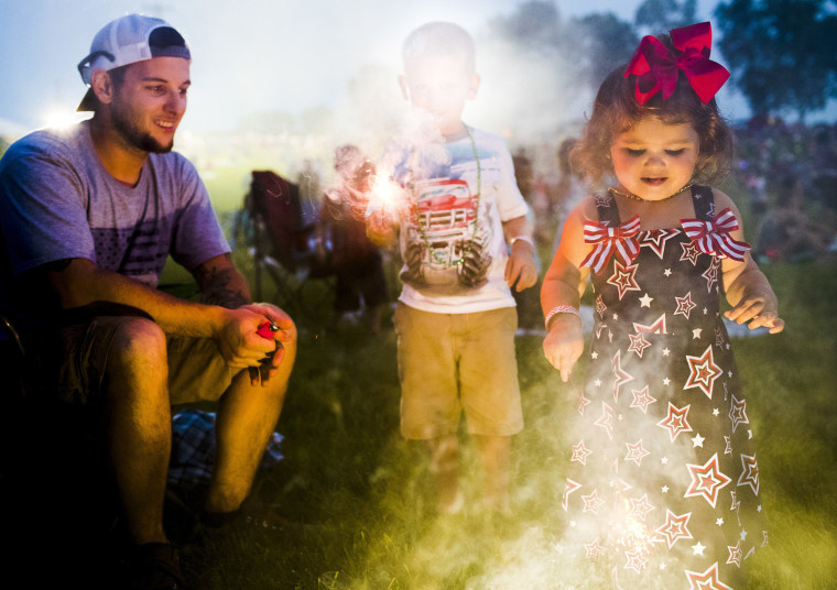 Image: Ashlynn Zinman, 2, from right, plays with sparklers with her brother, Carson Zinman, 5, and father Anthony Zinman,