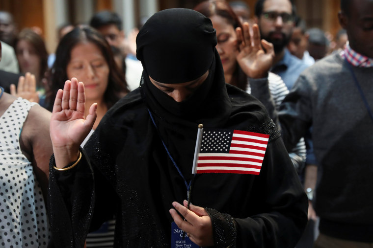 Image: Immigrants hold their hands up during the Pledge of Allegiance at a U.S. Citizenship and Immigration Services Naturalization ceremony in the New York Public Library in New York