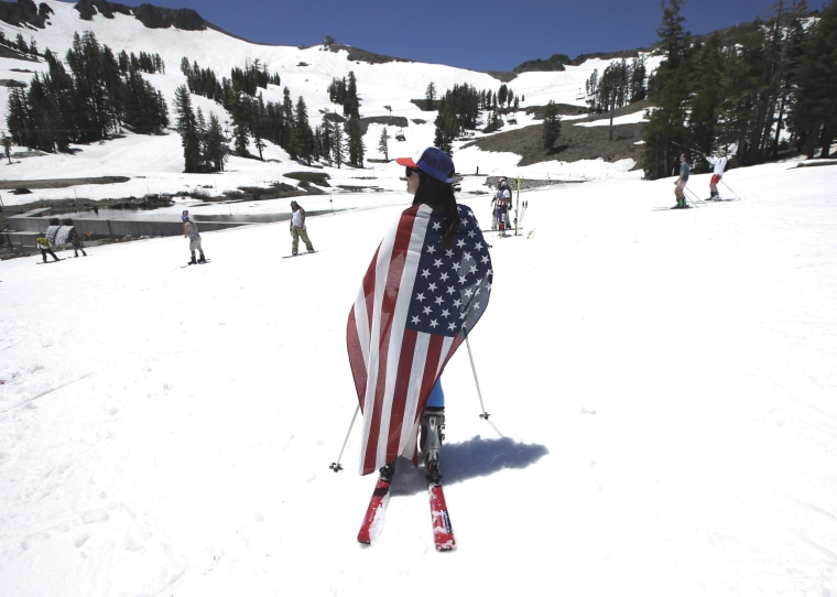 Image: Draped with an American flag, Kate Kunkel takes a break from skiing at Squaw Valley Ski Resort