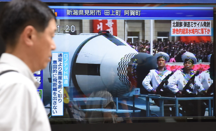Image: A pedestrian walks past a screen broadcasting file news footage of a military parade showing North Korean soldiers and a missile, after a ballistic missile was launched by North Korea