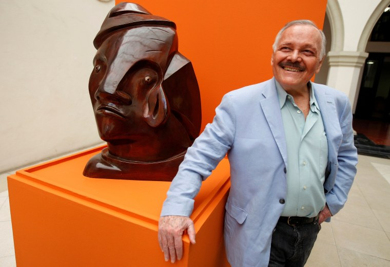 Image: FILE PHOTO: Mexican drawer, engraver and sculptor Cuevas poses next to a bronze sculpture during a media tour in Monterrey