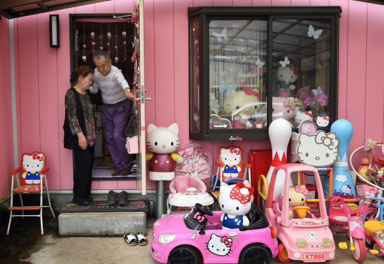 Image: Retired Japanese police officer Masao Gunji posing with his Hello Kitty collection