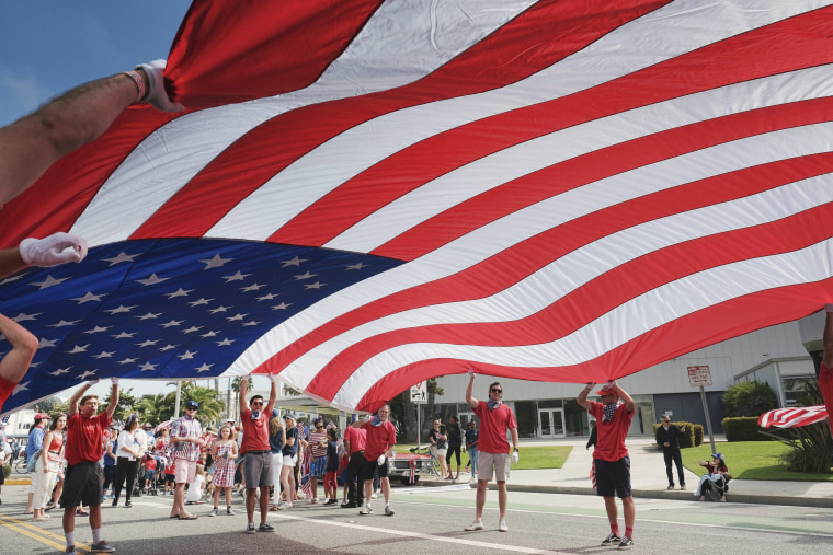 Image: Participants carry an American flag during the 4th of July parade in Santa Monica