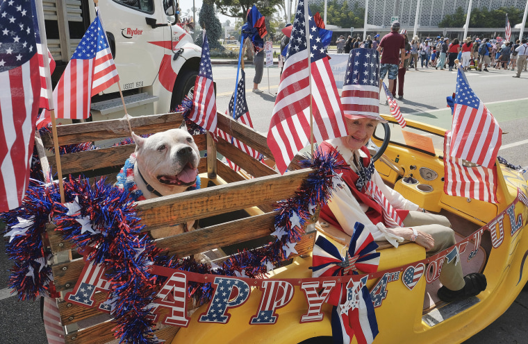 Image: Jasper, a 10-year-old Pit Bull, shares a ride in an electric vehicle with Ellen Brennan during the 4th of July parade