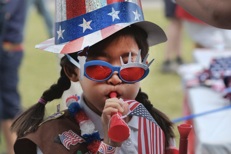 Image: Eight-year-old Hana Cho from Girl Scout Troop 5665 tests out a horn prior to participating the Fourth of July parade in Santa Monic
