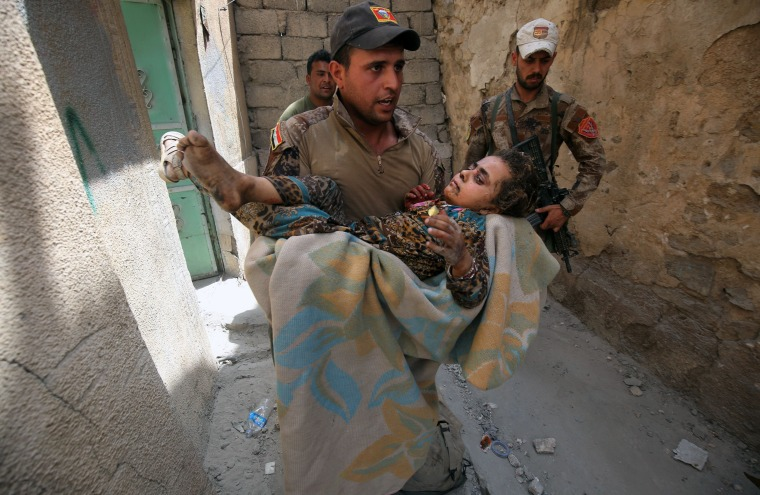 Image: A member of the Iraqi Counter-Terrorism Service (CTS) carries a wounded displaced girl in the Old City of Mosul