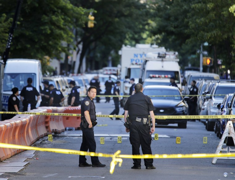 Image: Numbers mark a crime scene near the site where a police officer was fatally shot in the Bronx