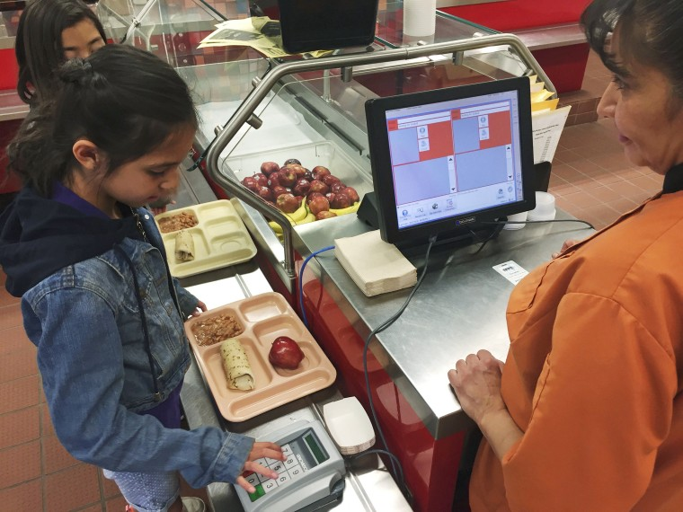 Image: third grader Elliana Vigil punches in her student identification meal to pay for a meal at Gonzales Community School