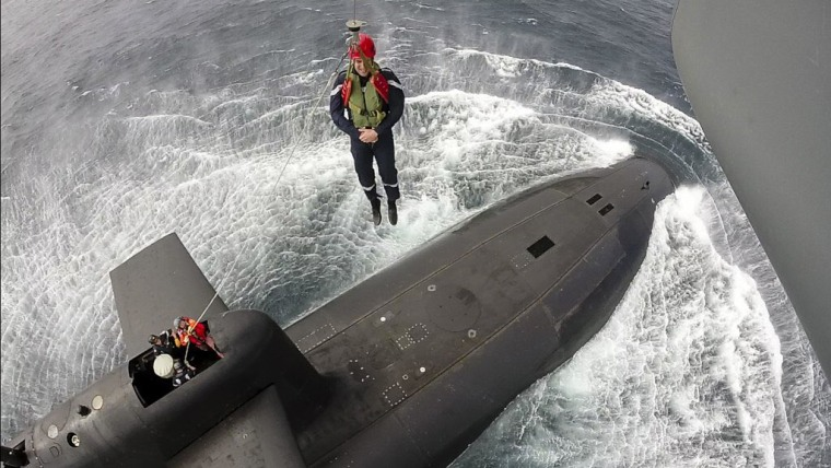 French President Emmanuel Macron is lowered from a helicopter to a nuclear submarine in the Atlantic.