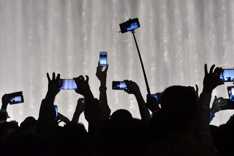 Image: People take photos and video with their phones