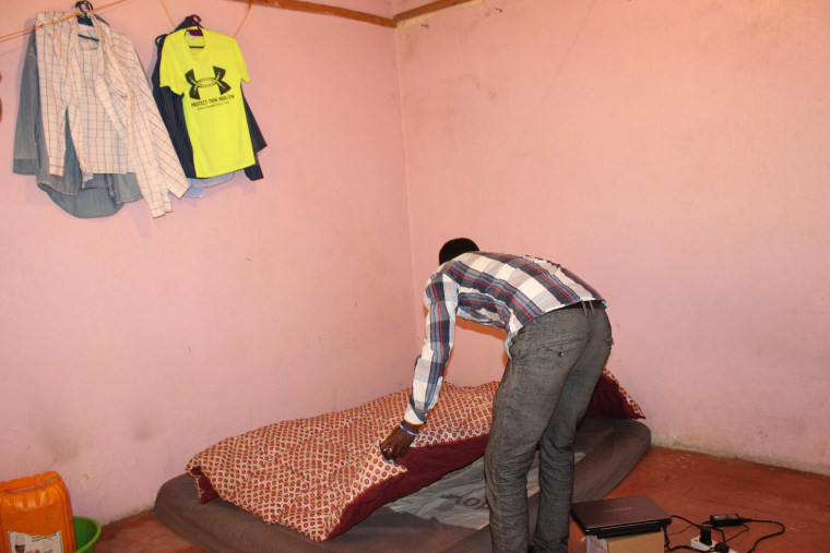 Yusuf making her bed in the one-room house she shares with three others in Rongai, Kenya.