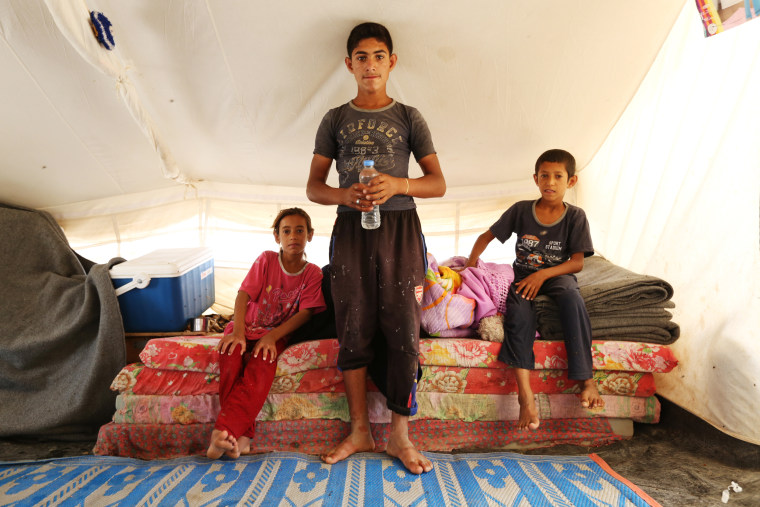 Image: Atallah Saleh, 15, stands inside a tent with his siblings at the Hammam al-Alil refugee camp in northern Iraq