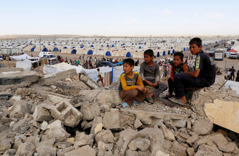 Image: Displaced Iraqi children who fled their homes sit on debris outside Hammam al-Alil camp south of Mosul