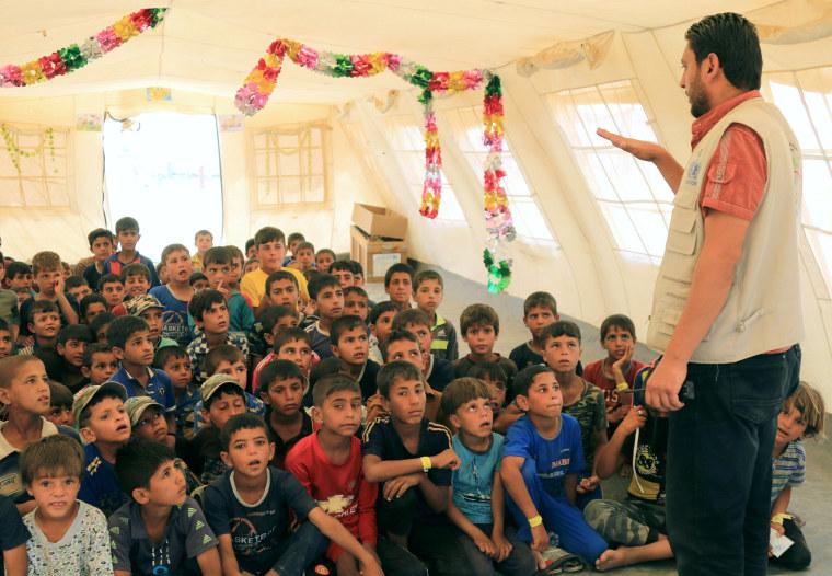 Image: Zaid Adil Sultan teaches a class for displaced Iraqi children in a tent school at tje Hammam al-Alil camp