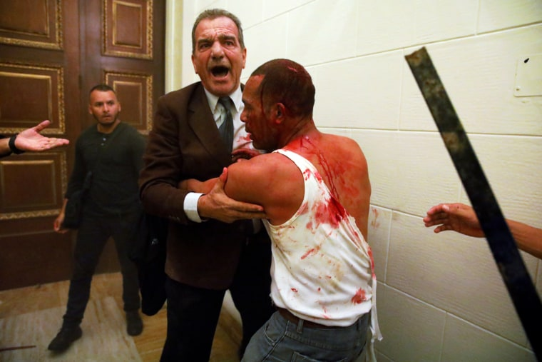 Image: Opposition lawmaker Stefanelli holds an injured government supporter after he and a group of fellow government supporters burst into Venezuela's opposition-controlled National Assembly during a session, in Caracas