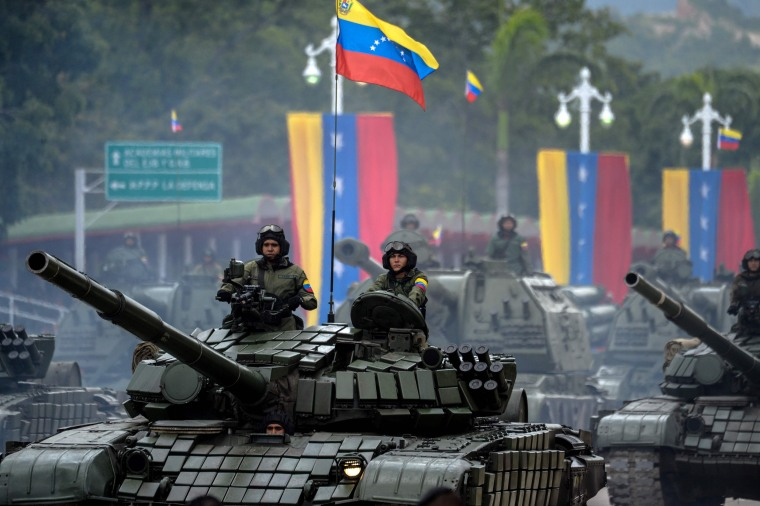 Image: Venezuelan Russian-made Mi-17 helicopters overfly a column of T-72B tanks during a military parade