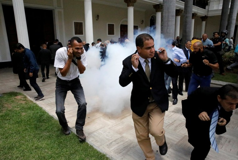 Image: People react as a firecracker explodes outside the National Assembly, in Caracas