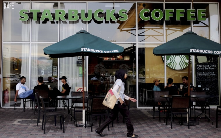 A Muslim woman walks past a Starbucks Coffee shop in Rawang outside Kuala Lumpur, Malaysia, Thursday, July 6, 2017. Muslim groups in Malaysia and Indonesia have called for a boycott of Starbucks because of the coffee chain's support for LGBT rights.