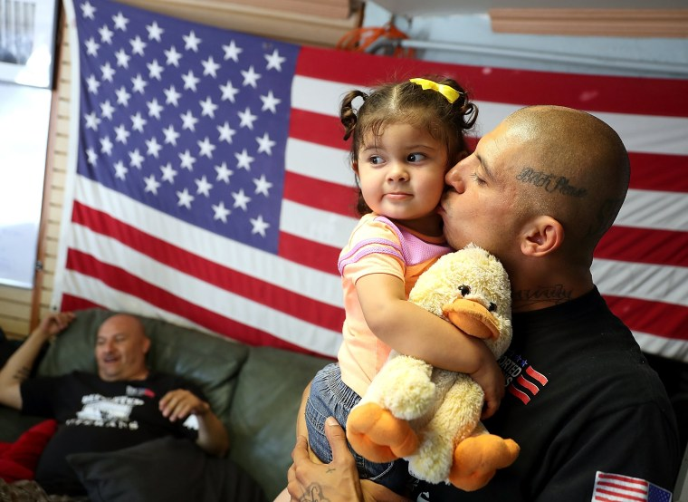 Image: A veteran kisses his daughter