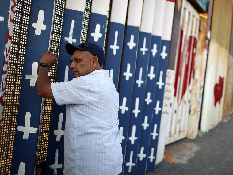 Image: A veteran looks through the border fence