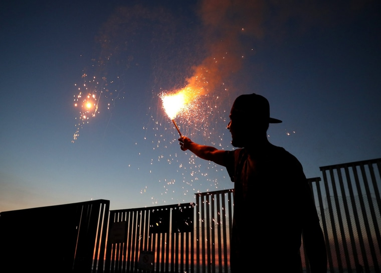 Image: A man shoots off fireworks next to the US-Mexican border fence.