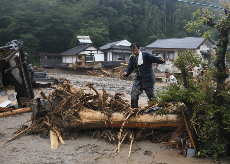 Image: A resident makes his way back to his home after an overnight evacuation caused by torrential rain at Hoshimaru district in Asakura