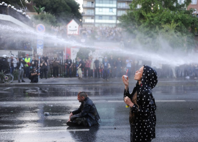 Image: A protester blows bubbles as riot police use water cannons