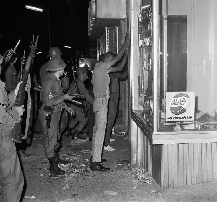 Image: National guardsmen search several people arrested