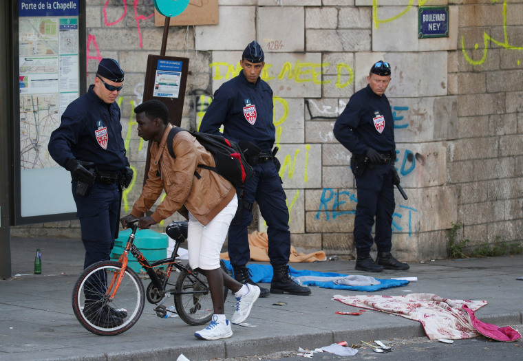 Image: A migrant rides his bike past French police