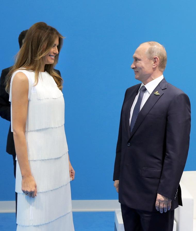 Image: Russian President Vladimir Putin (R) and US First Lady Melania Trump (L) meet