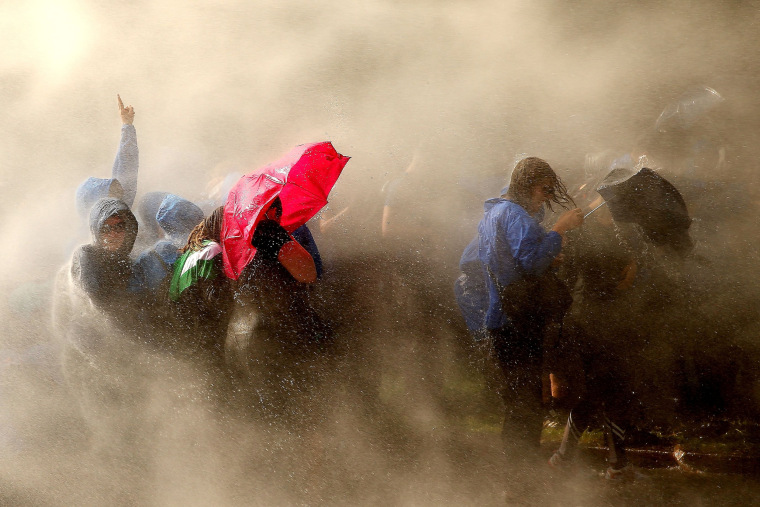 Image: Demonstrators are hit by water cannons of the police as they protest