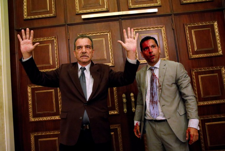 Image: Opposition lawmaker Stefanelli gestures next to fellow opposition lawmaker Leonardo Regnault after a group of government supporters burst into Venezuela's opposition-controlled National Assembly during a session, in Caracas