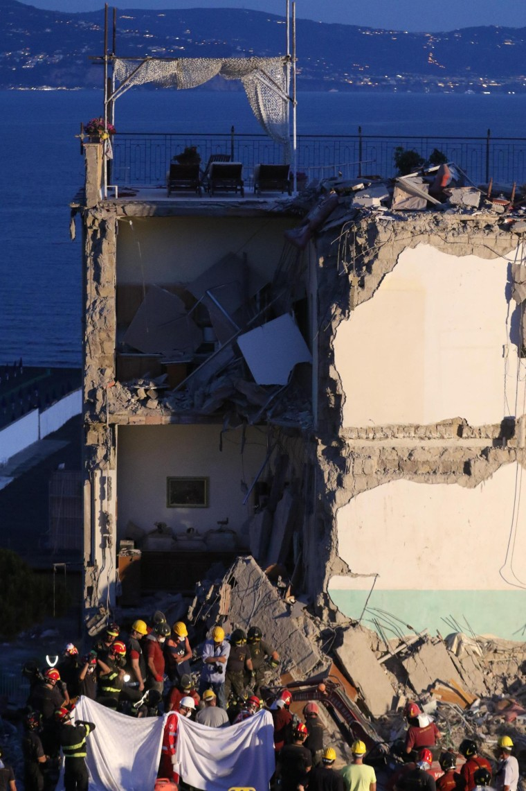 Image: Rescuers at work amid the rubble of the collapsed building in Torre Annunziata.