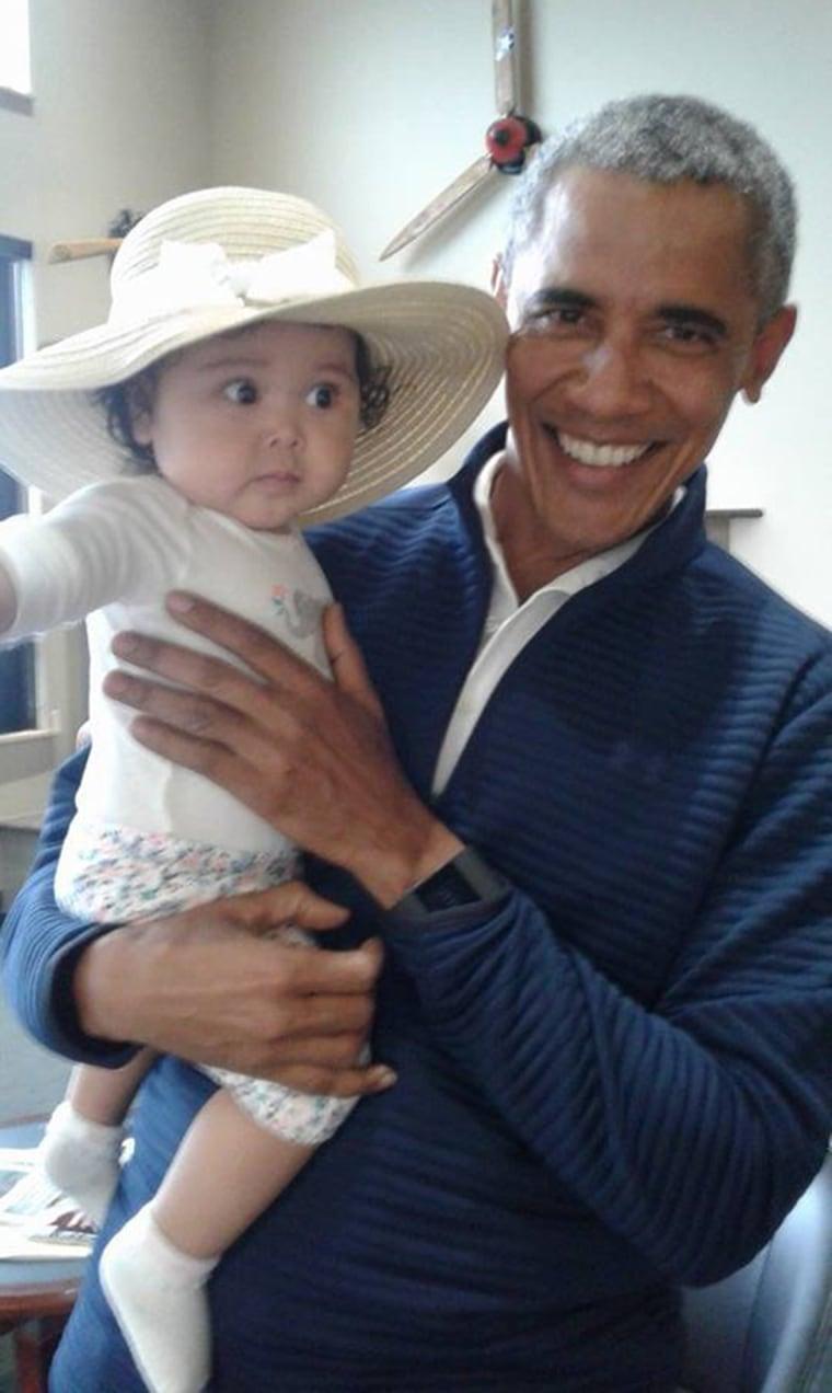 Image: Former U.S. President Barack Obama holds Giselle Jackinsky at Anchorage International Airport in Alaska