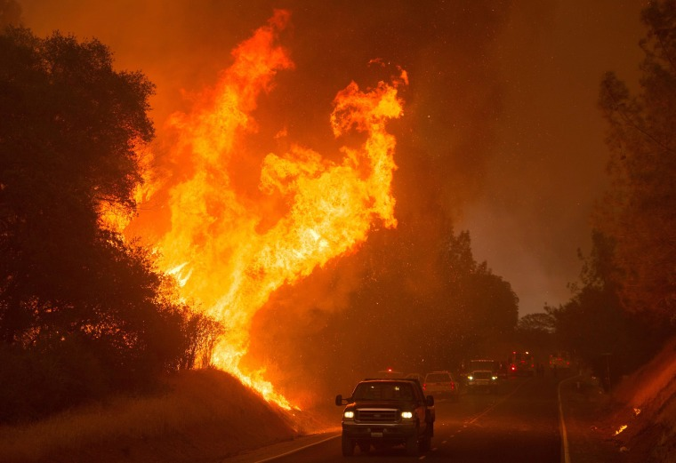 """Image:  Motorists drive past flames from the \""""Wall Fire\"""" along Forbestown Road in Oroville, California"""
