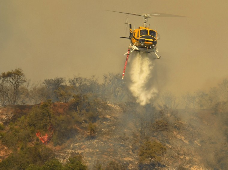 Image: A helicopter makes a water drop near Cachuma Lake in Los Padres National Forest as the 'Whittier' wildfire burns in Santa Barbara County, California