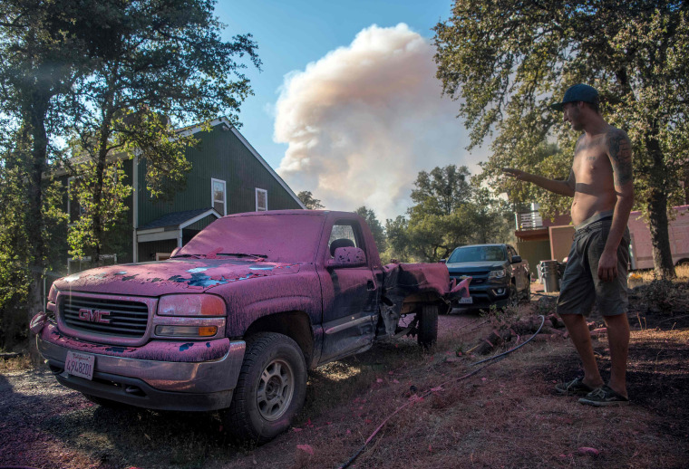 Image:  Sean Greenlaw views his truck covered in fire retardant as a smoke plume billows in the background near Oroville