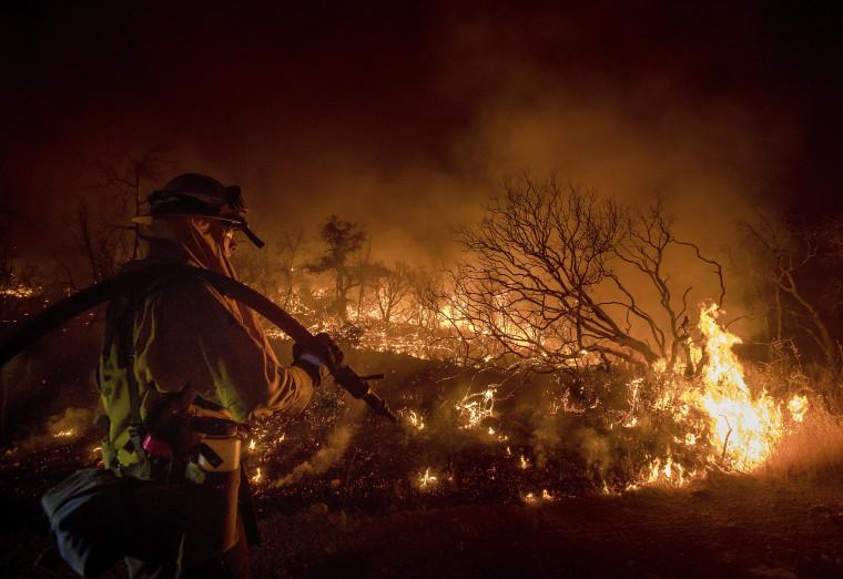 Image: Firefighter Kern Kunst battles the Wall fire near Oroville, California