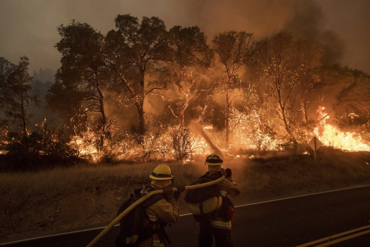 Image: Firefighters battle a wildfire as it threatens to jump a road near Oroville, California